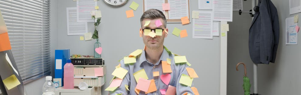 Office worker sitting at desk covered with colorful post it stick notes.