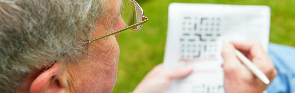 senior man doing crossword in garden